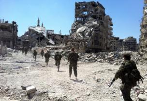 Syrian government forces patrol near damaged buildings in Khalidiya, Homs (28 July 2013)