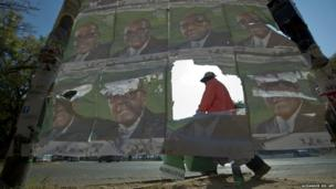 A Zimbabwean on his way to work walks pass posters of President Robert Mugabe in Harare