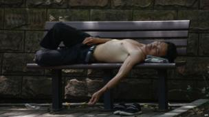 A man takes a rest in a park from the heat in Shanghai, 2 July 2013