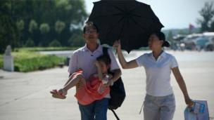 A woman (R) holds an umbrella over a man (L) as he holds his daughter while walking along a street in Beijing, 28 July 2013