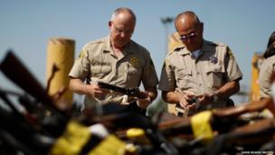 Deputies look at guns which are to be melted