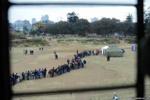 Zimbabweans line up in front of a temporary polling station in Harare