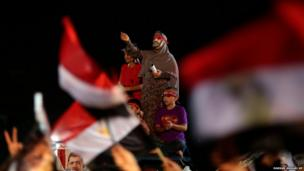 A supporter of Egypt's ousted President Mohammed Morsi wears a mask and chants slogans
