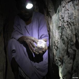 A mine worker displays a gold rock inside a local mine in Al-Ibedia locality at River Nile State on 30 July 2013