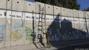 """An Israeli soldier removes a ladder placed by Palestinian males (not seen), not permitted to cross into Jerusalem from the West Bank by Israeli security forces, after they used it to climb over Israel""""s controversial barrier, in the village of Al-Ram near Ramallah, during the Muslim holy month of Ramadan August 2, 2013."""