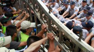 Protesters, left, try to open as policemen push back the front gate of Legislative Yuan ahead of an expected vote on a nuclear plant referendum in Taipei, Taiwan, Friday, Aug. 2, 2013.