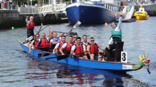 The German Dragon Boat team celebrating their victory on the River Lagan, winning their Dragon Boat Race competition.