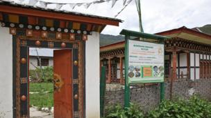 Entrance sign of Bumthang farm shop with prayer flags.