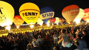 Hot air balloons and crowds watching