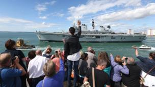 Crowds watch as the helicopter carrier HMS Illustrious leaves Portsmouth to take part in a deployment codenamed Cougar 13 in the Mediterranean and the Gulf (12 Aug 2013)