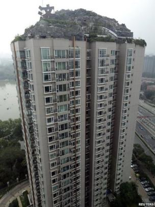 A privately built villa, surrounded by imitation rocks, is pictured on the roof of a 26-storey residential block in Beijing, 13 August 2013.