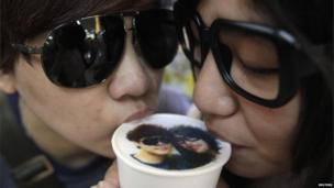 A couple drinks a cup of latte with their picture printed on top of the milk foam at a Family Mart in Taipei on 13 August 2013.