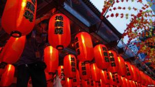 A man hangs up Chinese lanterns