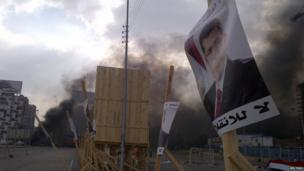 A poster of deposed Egyptian president Mohammed Morsi with plumes of black smoke during clashes between protesters and security forces in Cairo