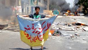 """A supporter of the Muslim Brotherhood and Egypt's ousted president Mohammed Morsi holds a banner reading in Arabic """"Alexandria is against the coup"""" as protestors set fire to a council building in Egypt's northern coastal city of Alexandria on 14 August 2013"""