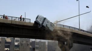 A police vehicle is pushed off of the 6th of October bridge by protesters close to the largest sit-in by supporters of ousted Islamist President Mohammed Morsi in the eastern Nasr City district of Cairo, Egypt, Wednesday, 14 August 2013