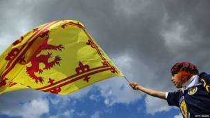 Fan waves flag in Trafalgar Square