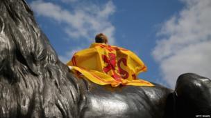 A Scotland fan sits on a statue in Trafalgar Square