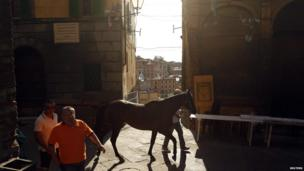 A horse is led through the streets of Siena in Italy after the fourth of six traditional horse races around the city's Del Campo square. Ten riders compete bareback to win the Palio, a silk banner depicting the Madonna and child.