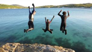 People jumping into the sea