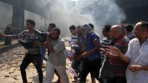 Egyptian Muslim Brotherhood supporters carry a wounded protestor in Cairo's Ramses square on 16 August, 2013.