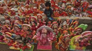 A child sits among idols of Hindu goddess Dashama left by devotees during the 10-day Dashama festival in Ahmedabad, India on 16 August 2013.