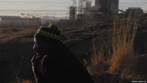 A man looks over the area where, a year ago, police shot 34 striking miners outside the Marikana platinum mine in South Africa on 16 August, 2013.