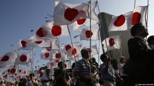 Supporters of Japan's nationalist movement carry flags as they mark the anniversary of the country's surrender in World War II in Tokyo on 15 August, 2013.