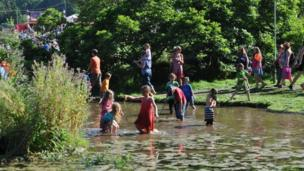 Children enjoy a paddle at Wales' Green Man live Music Festival on the Glanusk Estate in Powys