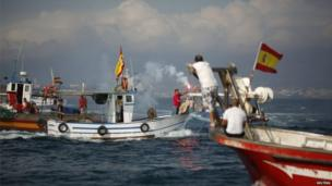Leoncio Fernandez, head of the La Linea fishermen, held a red flare to mark the end of the demonstration.