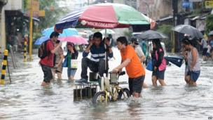 Residents wade through a flood street in Manila on 19 August