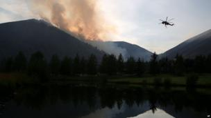 A helicopter descends to refill with water from a pond while battling the Beaver Creek Fire, north of Hailey, Idaho on 17 August 2013