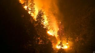 Fire creeps slowing down the western canyon wall above the Wood River in Hailey where firefighters continue to battle the Beaver Creek Fire 17 August 2012