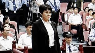 In this 9 August 2012 file video image taken from CCTV, Gu Kailai, centre, the wife of disgraced politician Bo Xilai, stands during her trial in the Hefei Intermediate People's Court in Hefei in eastern China's Anhui province