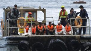 Australian customs officials and navy personnel escort asylum-seekers onto Christmas Island 21 August, 2013, after they were rescued by the Australian Navy ship HMAS Parramatta from a crowded boat that had foundered at sea