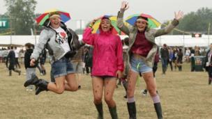 Three girls jumping in the rain