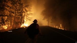 A firefighter walks down Highway 120 while fighting Rim Fire in California on 25 August 2013