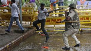 Supporter of World Hindu Council and an Indian policeman clash during a protest in Delhi, India