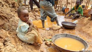 Four-year-old girl in Tanzania plays in an amalgamation pond contaminated with mercury while adults process gold at a gold rush site in Shinyanga Region, Tanzania. © 2012 Zama Coursen-Neff/Human Rights Watch