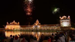 Golden temple lit up at night with fireworks bursting above it