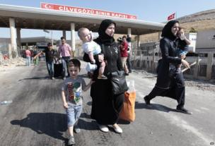 Syrian refugees pass through the Turkish Cilvegozu gate border, Saturday, Aug. 31, 2013.