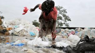 A woman cleans plastic bags bound for recycling in Yopougon
