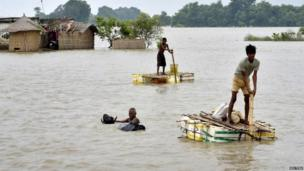 Flood-affected villagers use temporary rafts as they navigate through the floodwaters of river Ganges and move to safer grounds, after heavy rains at Patna district in the eastern Indian state of Bihar