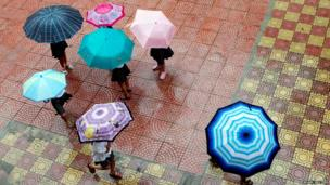 Pupils walk with umbrellas in the rain on the first day of the new school year at the Nam Thanh Cong school in Hanoi
