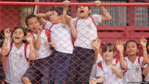 Children cheer on the Brazilian national football players