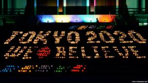 A man walks past an illuminated sign reading Tokyo 2020 We Believe which is made from 2,020 candles at Zojoji temple in Tokyo