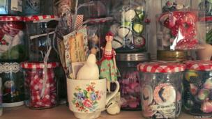 Close-up of jam jars of textiles, fabric scraps, baubles and badges in Sophie Tilley's studio