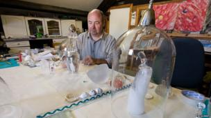 Bill Swann looks at one of his glass creations in his Porthmadog studio