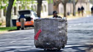 A man pushes a bag of recyclable goods outside South African anti-apartheid icon Nelson Mandela's home in Houghton, Johannesburg - Tuesday 3 September 2013