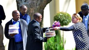 A women gives flowers and a cake to security personnel outside Nelson Mandela's home in Johannesburg